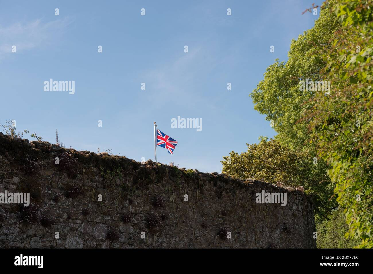 Single red, white and blue Union Flag of the United Kingdom flying from pole above stone wall against background of blue sky. Stock Photo