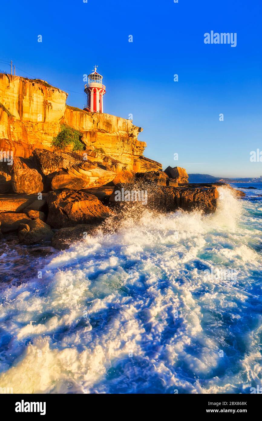 Stripped white-red Hornby lighthouse at the entrance to Sydney harbour from Pacific ocean in soft morning light against clear blue sky. Stock Photo