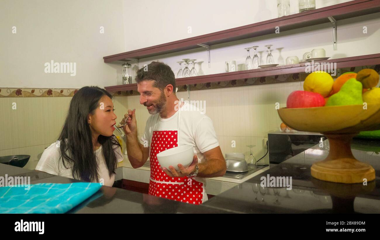 young beautiful and happy mixed ethnicity couple in love cooking together at home kitchen the caucasian husband in red apron and his Asian wife tastin Stock Photo
