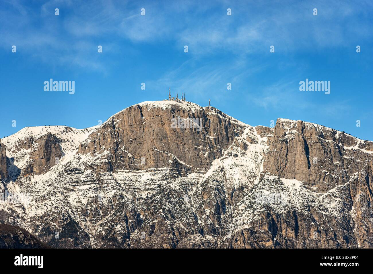 Peak of the Paganella or cima Roda (2125 m), snow caped Alps with the antennas of the weather station, seen from the Trento, Trentino, Italy. Stock Photo