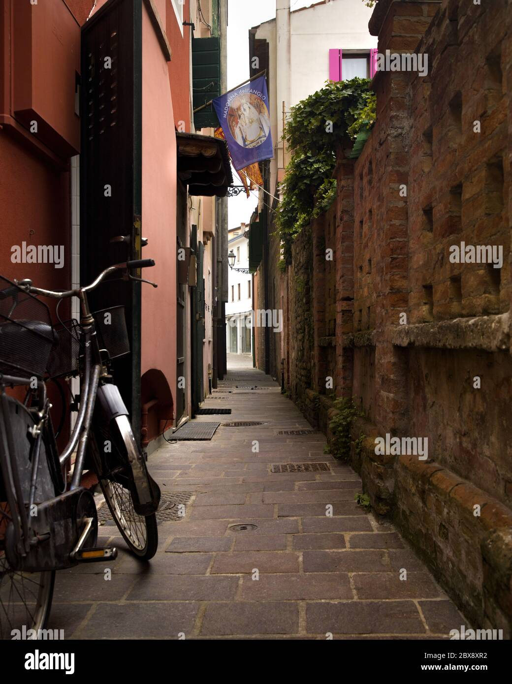 Tourism in Veneto and point of interest among the narrow alleys  and maritme houses to Caorle seaport with bicycles  and colored houses. Stock Photo