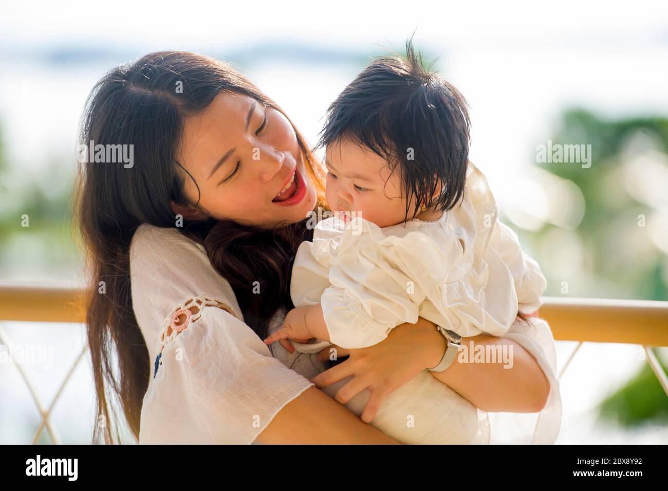 young happy and beautiful Asian Korean woman playing and holding sweet adorable baby girl sitting at holidays resort enjoying summer vacation trip in Stock Photo