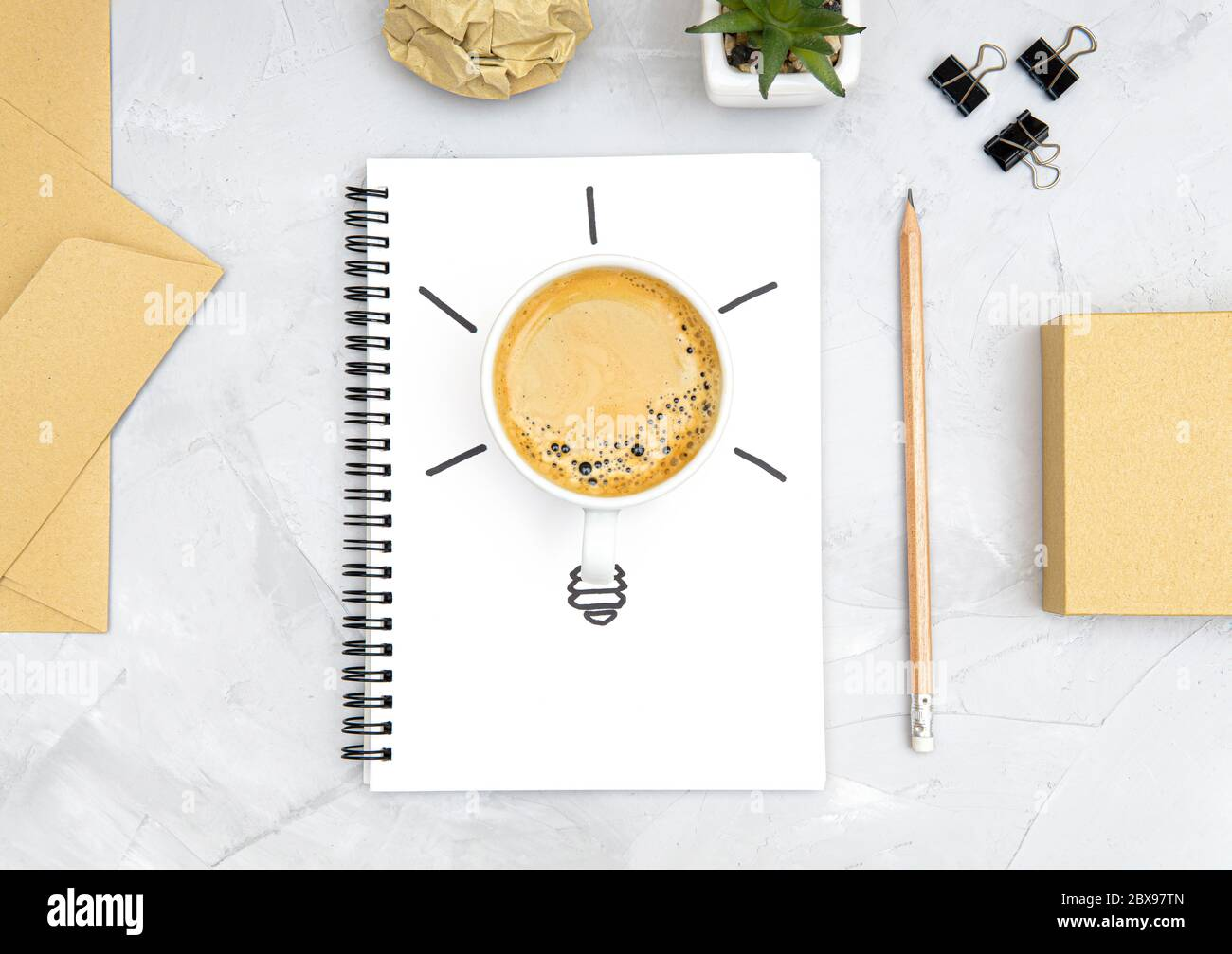 Light bulb symbol made of a fresh cup of coffee and a sketch on a spiral notebook. Office workplace flat lay. Refreshment and productivity concept. Bo Stock Photo