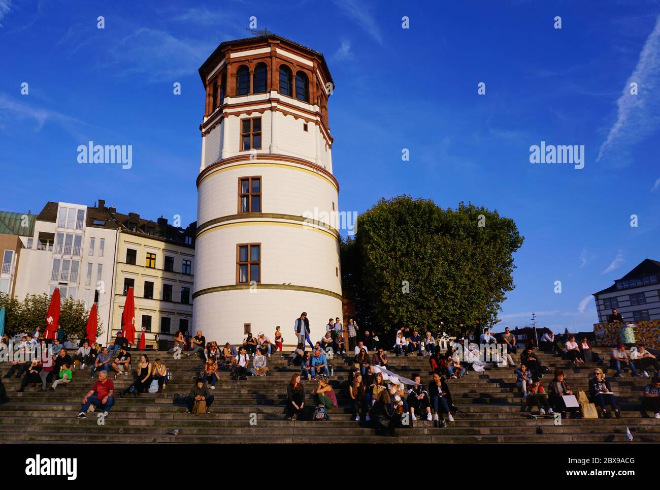 "The historic ""Schlossturm"" (castle tower) in Düsseldorf Old Town with people sitting on the steps and enjoying the sun. Stock Photo"