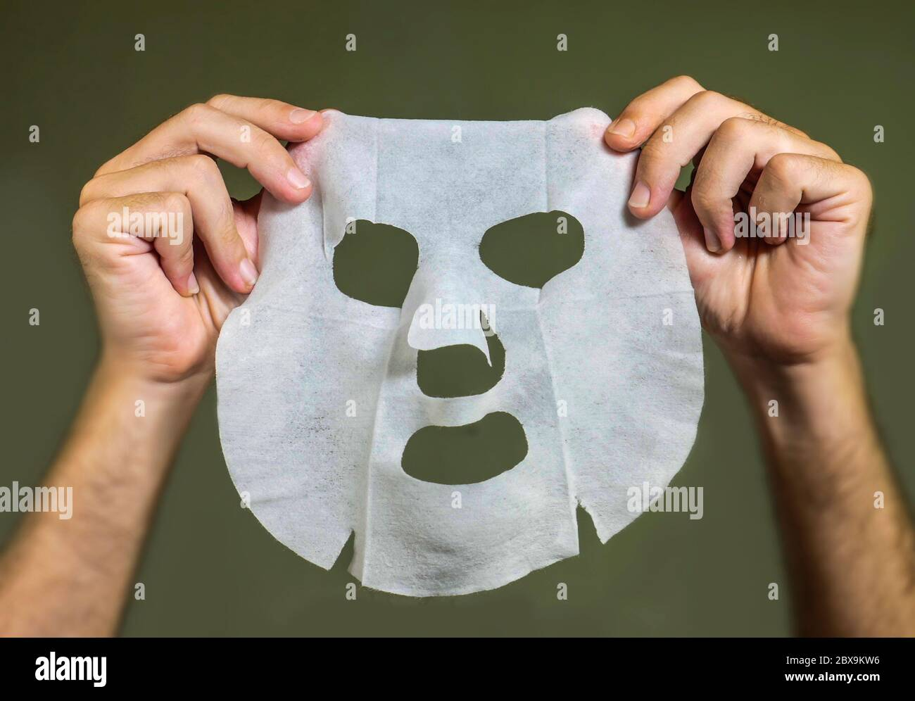 man hands holding beauty paper facial mask isolated on even background in face skin care concept Stock Photo