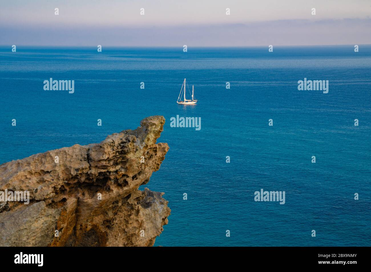View at the sea from rocks on a sailing boat Stock Photo
