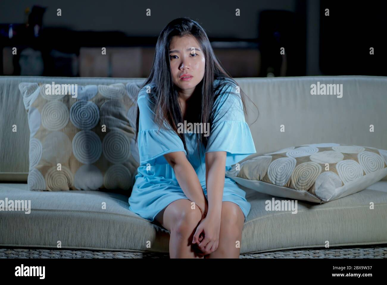 dramatic lifestyle portrait of young beautiful sad and depressed Asian Korean woman at home sofa couch feeling overwhelmed suffering anxiety crisis an Stock Photo