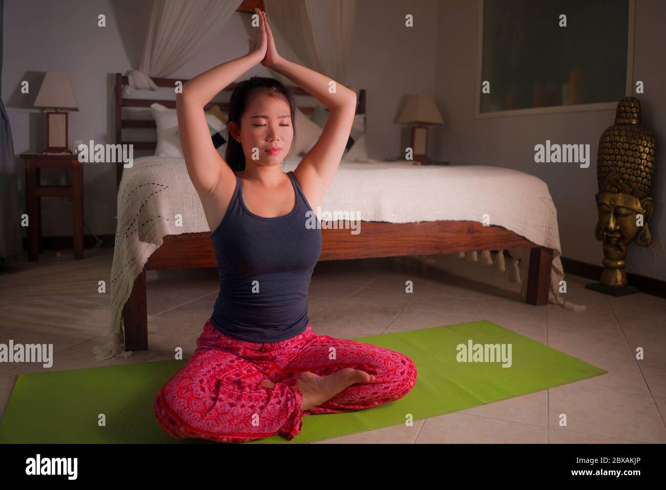 young happy and beautiful Asian Korean woman at home bedroom doing meditation workout on yoga mat relaxed and peaceful in wellness and healthy lifesty Stock Photo