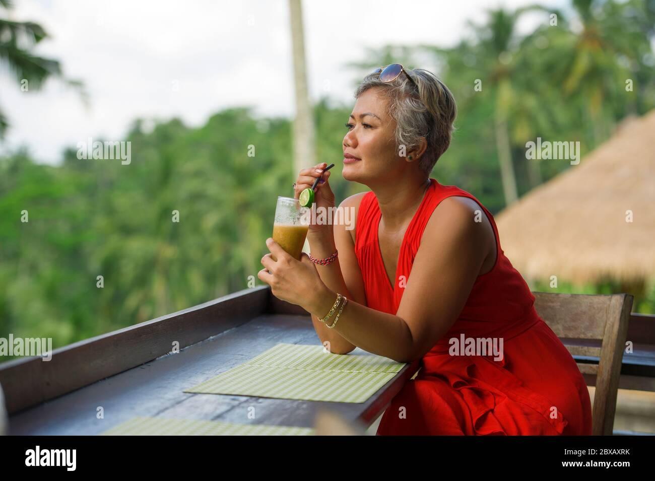 natural lifestyle outdoors portrait of attractive and happy middle aged Asian Indonesian woman in stylish red dress enjoying tropical holiday trip at Stock Photo