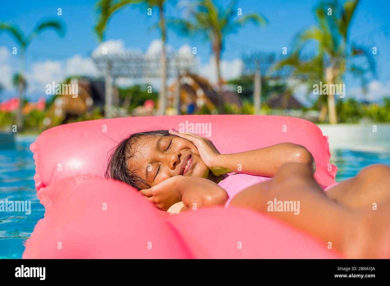 lifestyle outdoors portrait of young happy and cute female child having fun with inflatable airbed in holidays resort swimming pool smiling carefree a Stock Photo