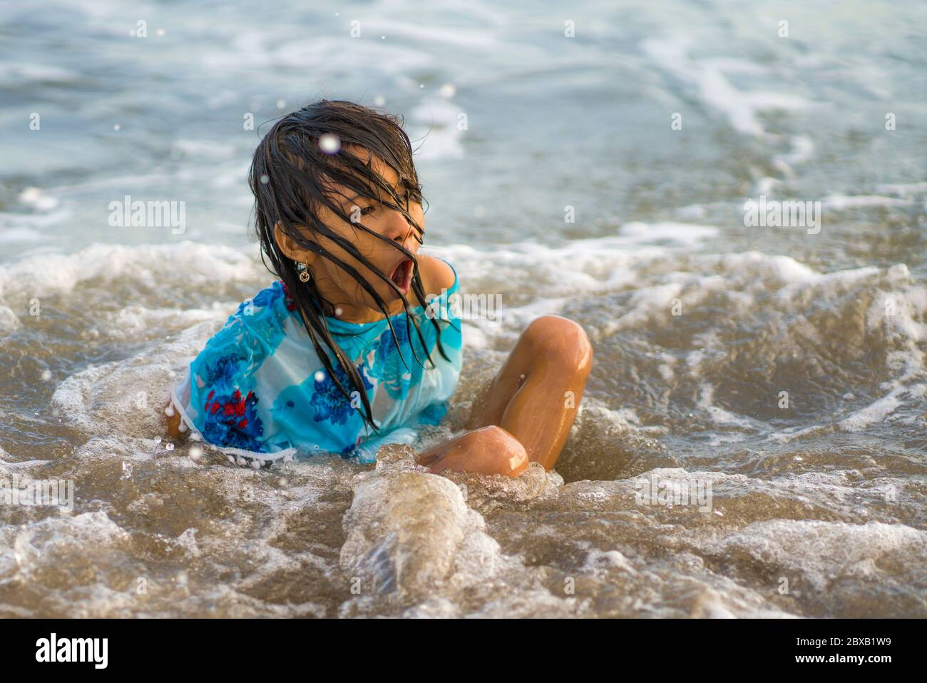 lifestyle candid portrait of young happy and excited child girl having fun at the beach swimming playing with sea waves enjoying crazy feeling free in Stock Photo