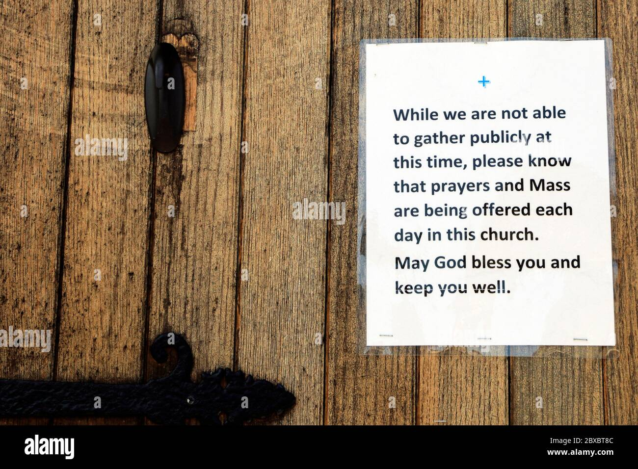 A church door indicating it is closed to its congregants due to Covid-19. A New Jersey government edict prohibited Mass for the masses. Stock Photo
