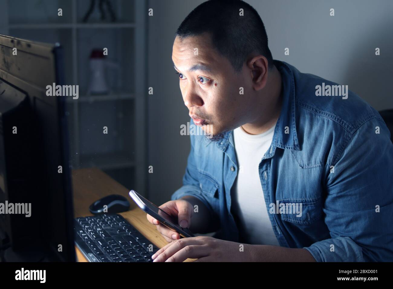 Young Asian man using smart phone and computer until late night, he is working or studying hard to reach his ambition. Student or businessman works ha Stock Photo