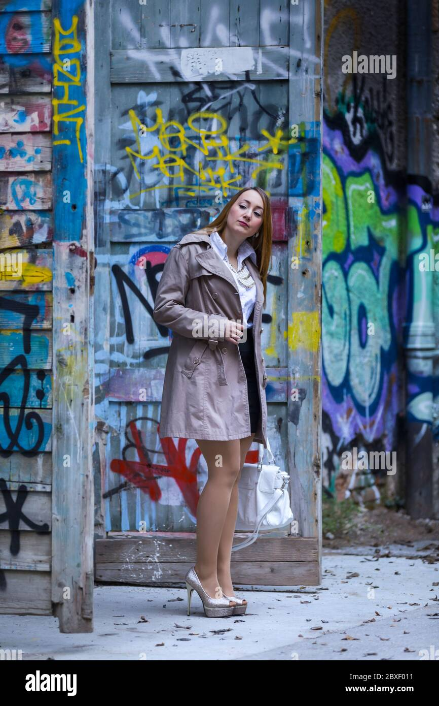 Female young woman 20-25yo 20-25 yo standing in abandoned building full of colorful graffiti artistry on walls whole body legs in sheer tights heels Stock Photo