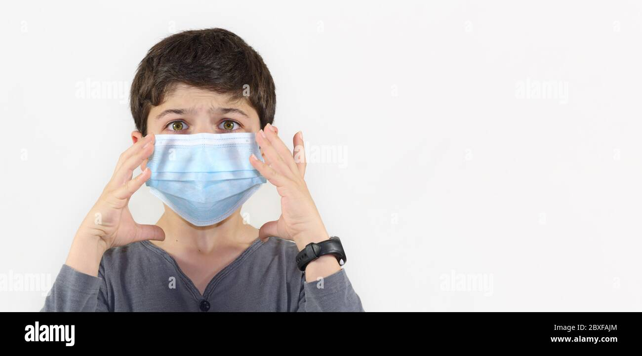 child with a surgical mask on the face - Covid-19 coronavirus barrier gesture child with surgical mask frightened by the epidemic Stock Photo