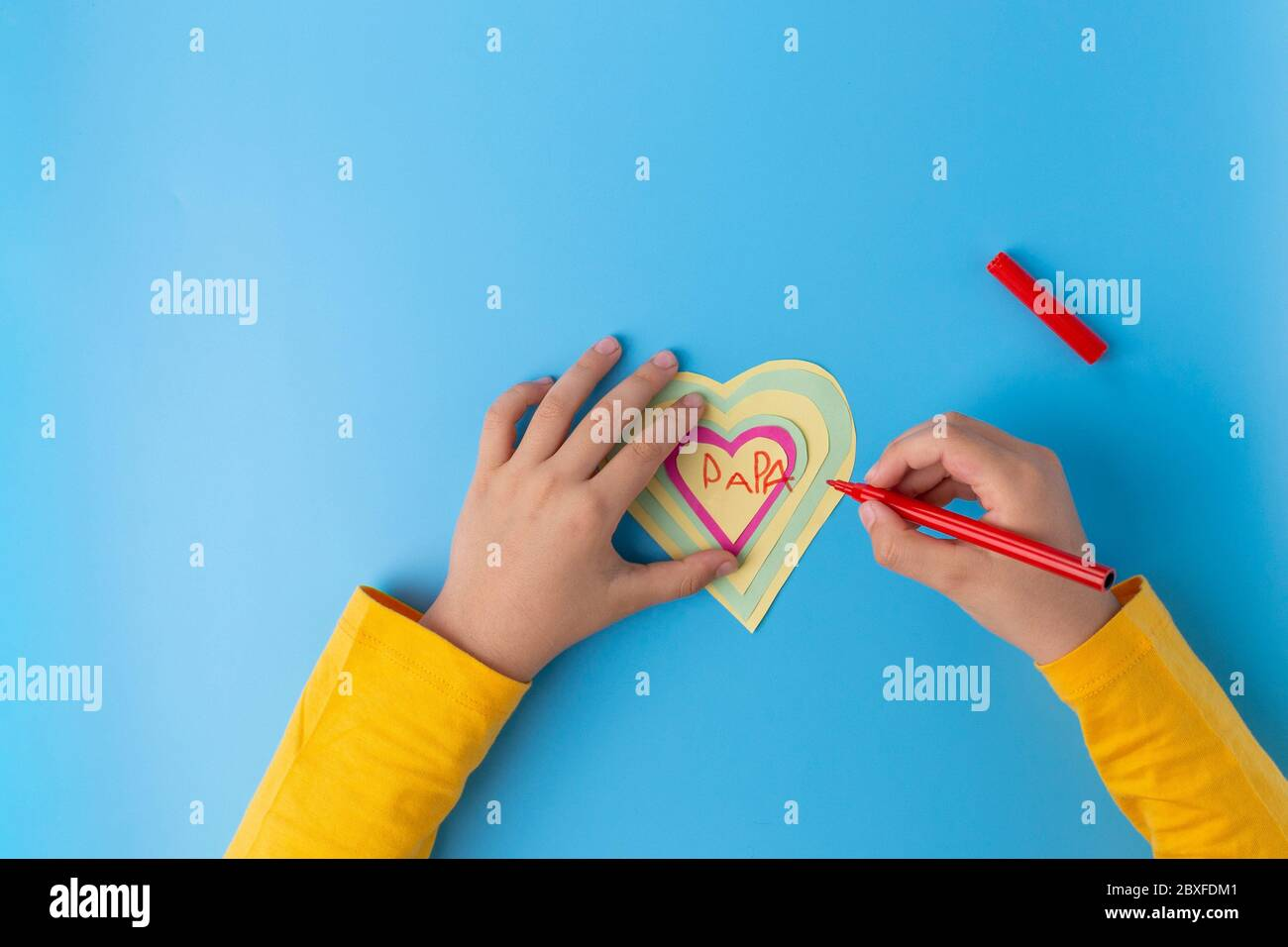paper craft fathers day card, kids made paper kids hand drowing heart on card Stock Photo