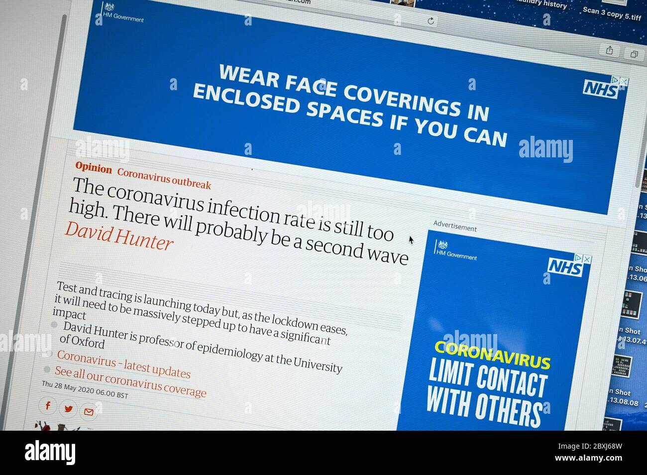 "UK government Covid-19 advert ""Wear face coverings in enclosed spaces"" next to an article ""infection rate still too high"". Stock Photo"