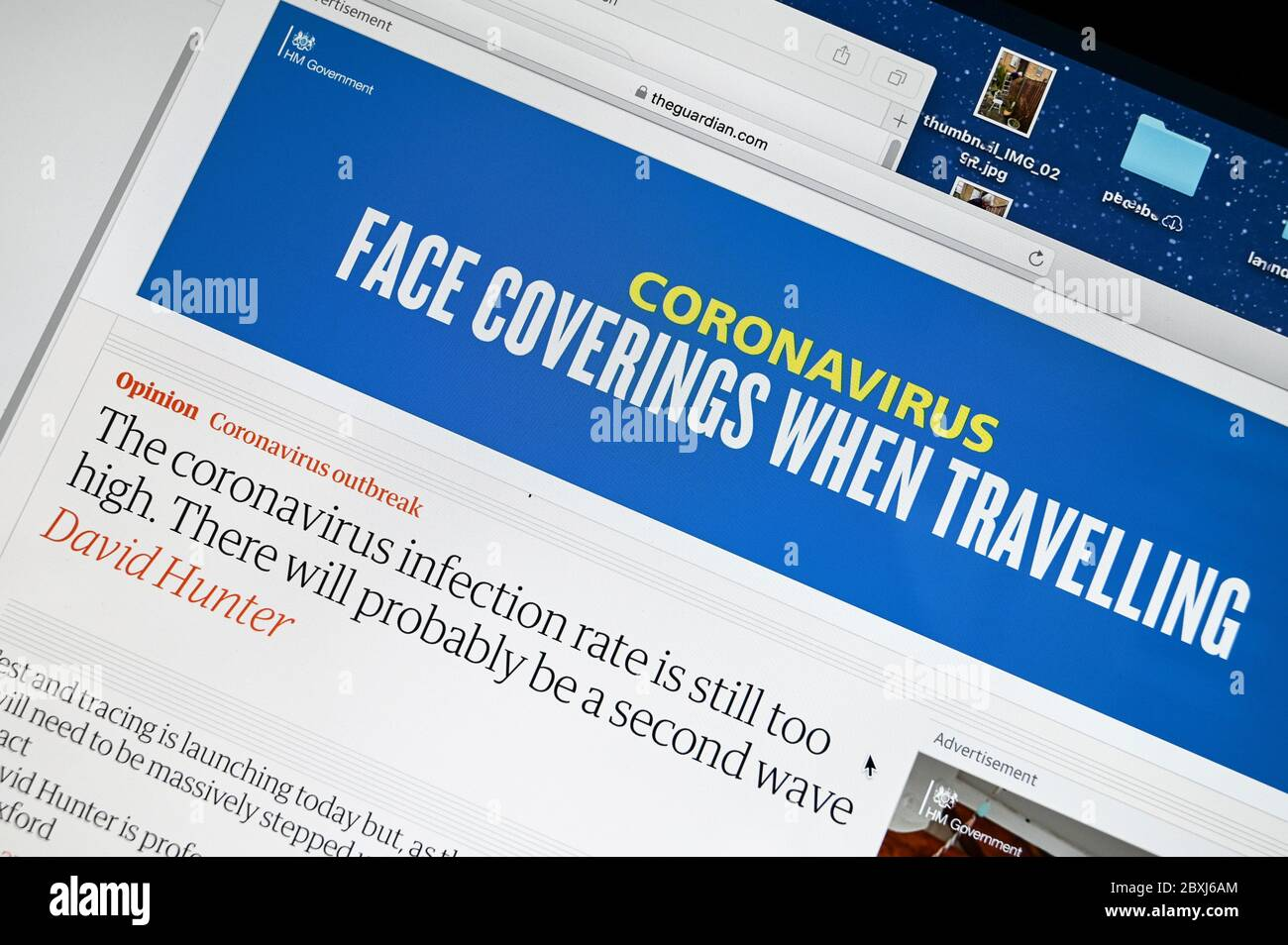 """UK Government Coronavirus public information advert """"Face coverings when travelling"""" above an article """"infection rate is still too high"""". Stock Photo"""