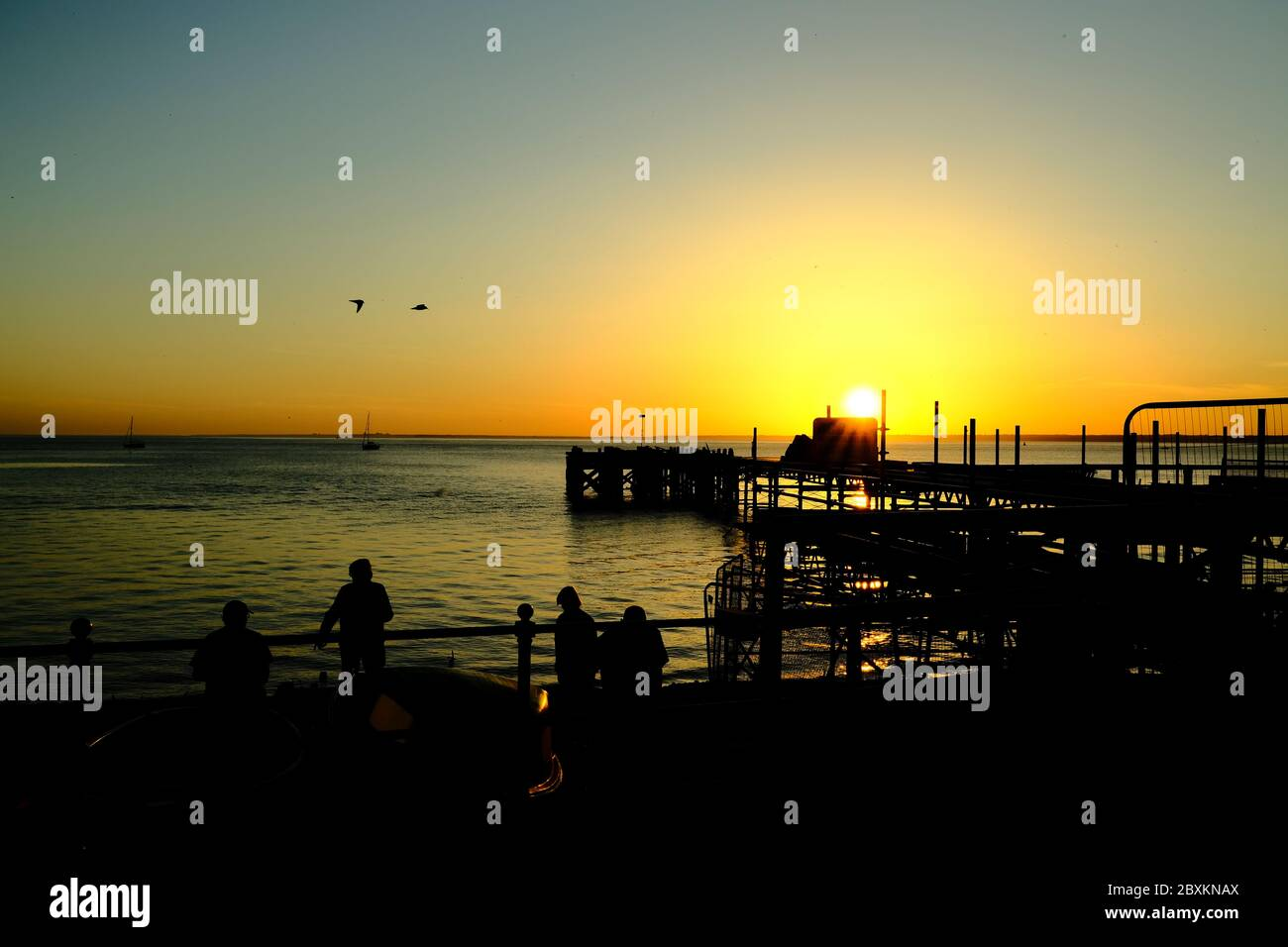 View out across the Solent to the mainland over Totland Pier isle of Wight at sunset yachts kayakers beachgoers in silhouette orange glow of twilight Stock Photo