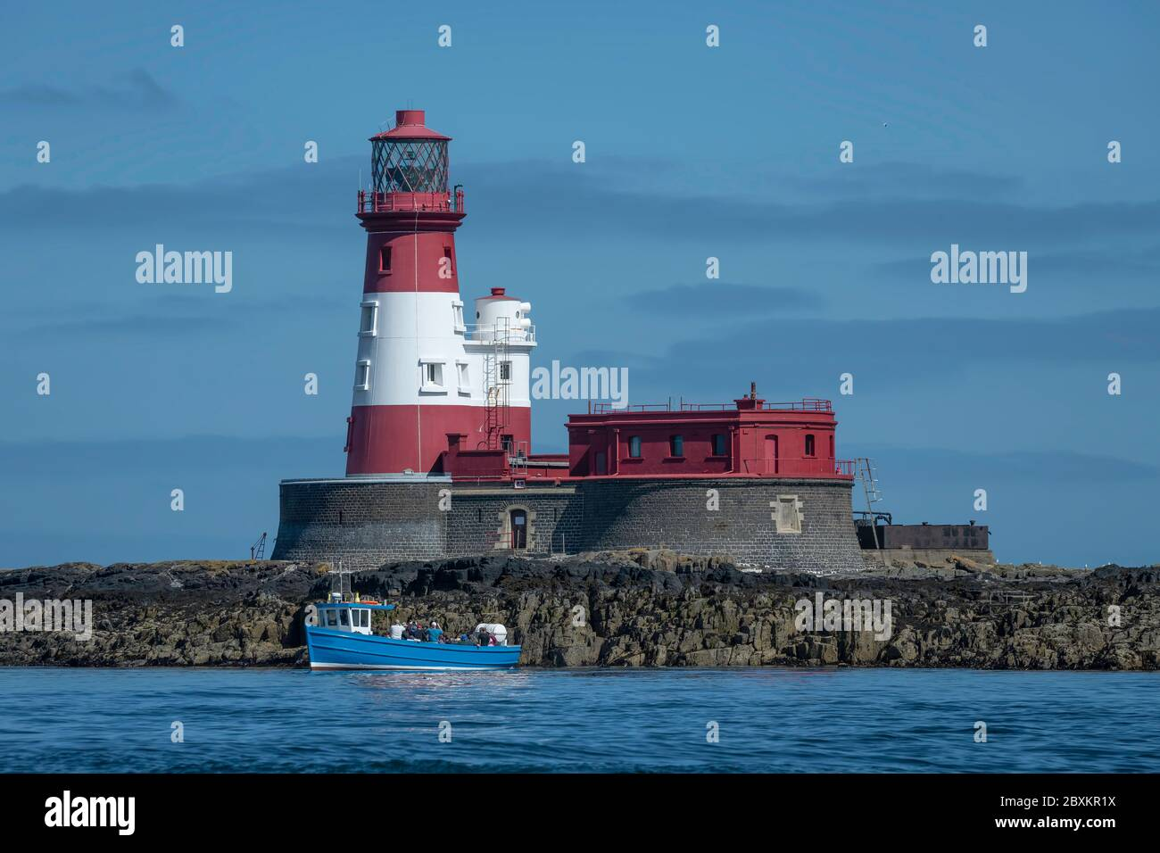 Longstone Lighthouse located in the Farne Islands of the United Kingdom with blue boat in front of it Stock Photo