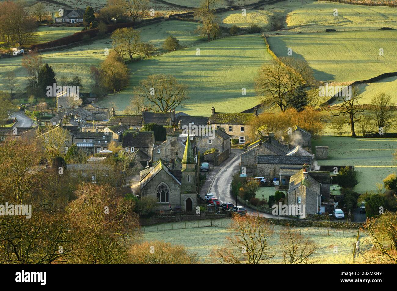 Burnsall (scenic Yorkshire Dales village) in valley, attractive cottages, country lane, green hillside fields (sunny winter morning) - England, GB, UK Stock Photo