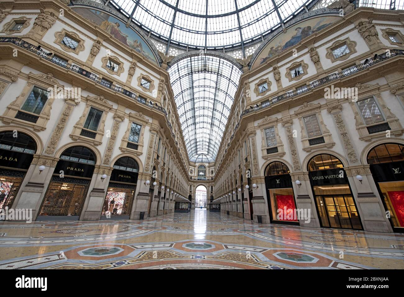 The emptiness of Galleria Vittorio Emanuele with shops closed during the lockdown caused by the Covid-19 in Milan, Italy. Stock Photo