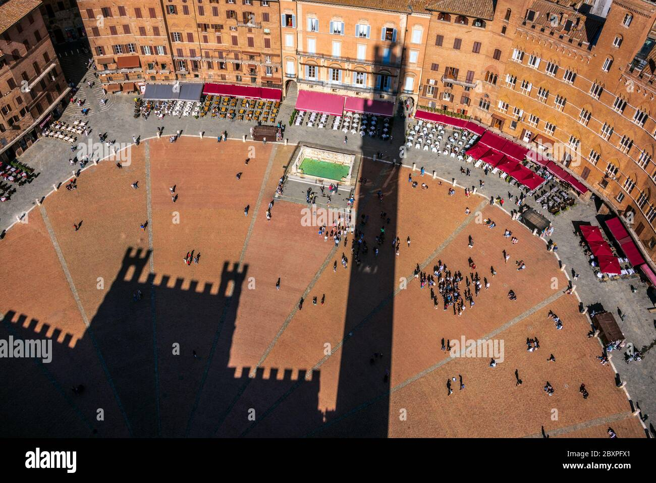 the town hall palace of Siena shot from high to bottom projected its shadows on the famous historical Campo city square Stock Photo