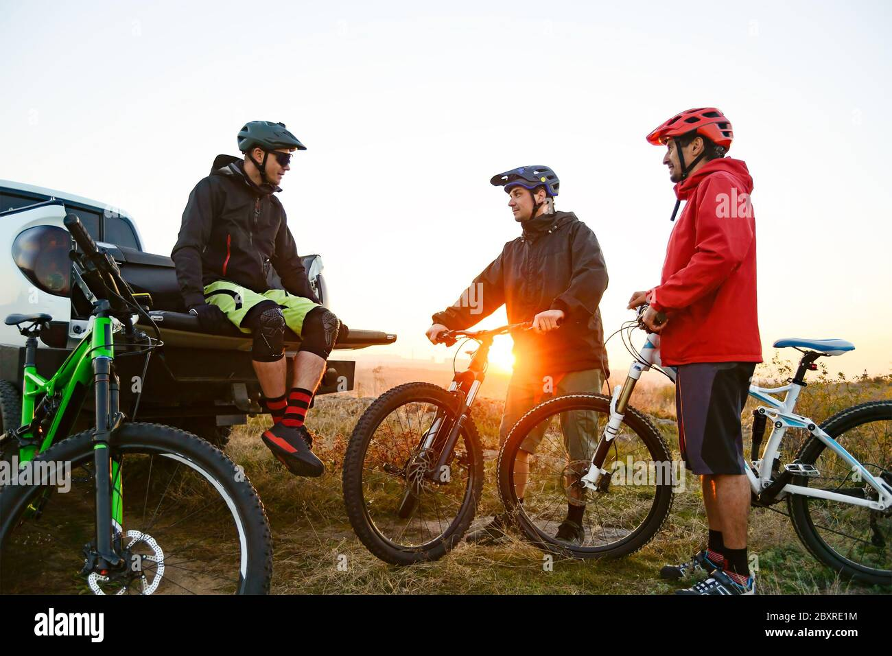 Friends Cyclists Resting near the Pickup Off Road Truck after Enduro Bike Riding in the Mountains at Warm Autumn Sunset. MTB Adventure and Car Travel Stock Photo
