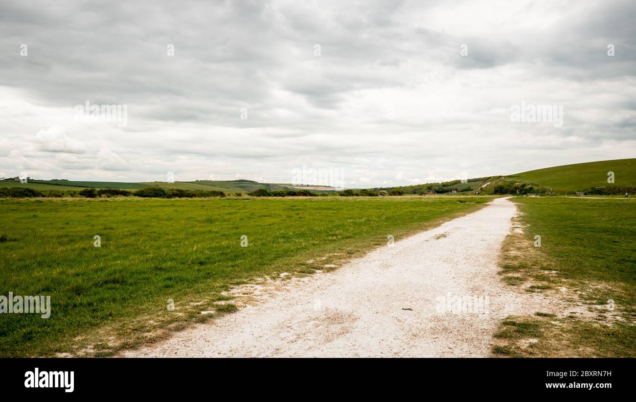 Cuckmere Haven flood plains, South Downs, England. A footpath leading into a view over Cuckmere Haven in East Sussex on the south coast of England. Stock Photo