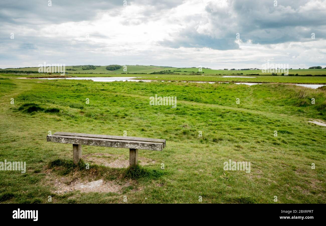 Bench with a view over the South Downs, England. The flood plains of Cuckmere Haven on the South Downs national park on the south coast of  England. Stock Photo