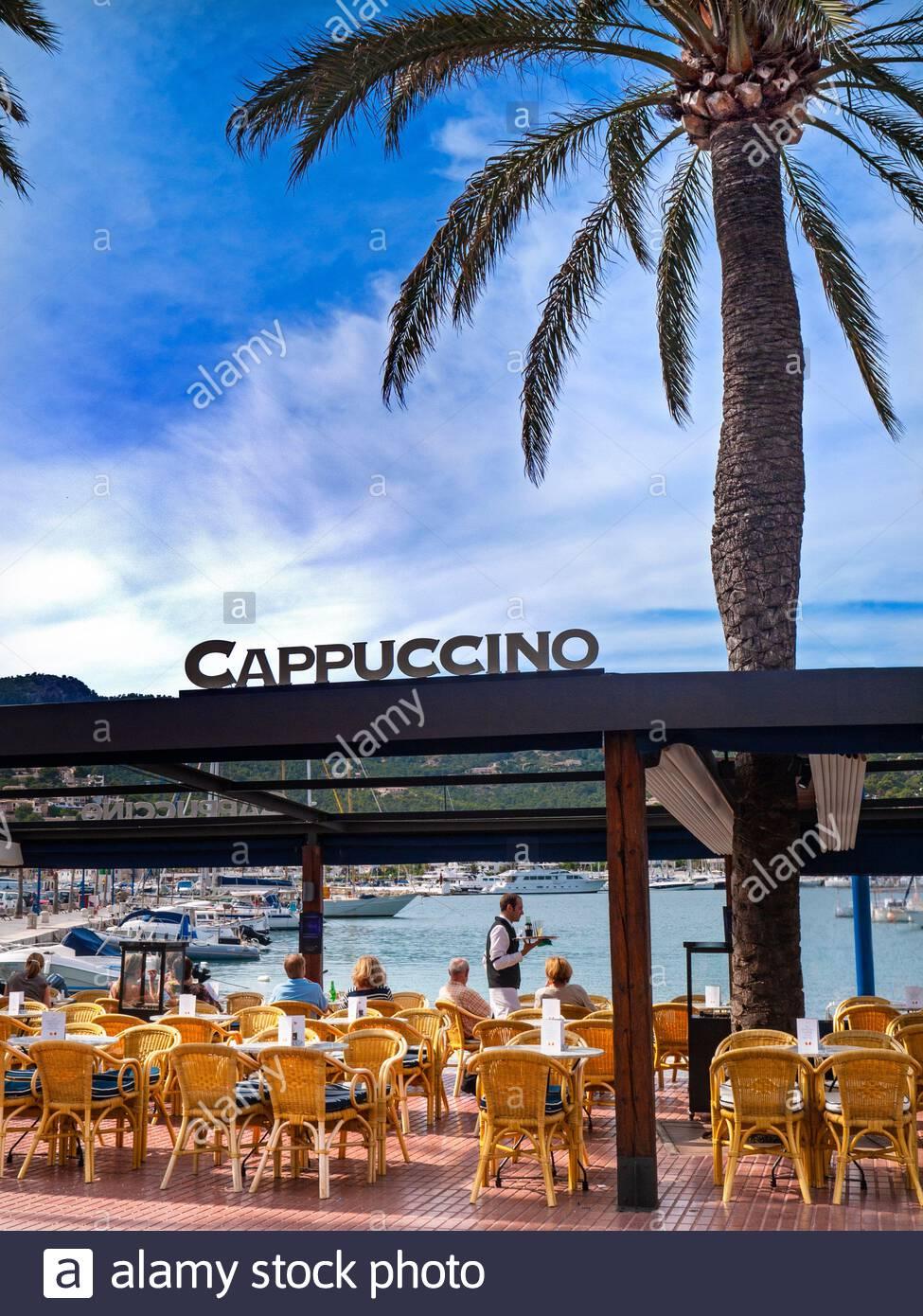 ANDRATX WAITER SERVICE MALLORCA SEAFRONT ALFRESCO BAR CAFE CAPPUCINO PALM TREE  Coastal alfresco luxury waterside Cappuccino Restaurant cafe and bar in Puerto Andratx Mallorca Balearic Islands Spain Stock Photo