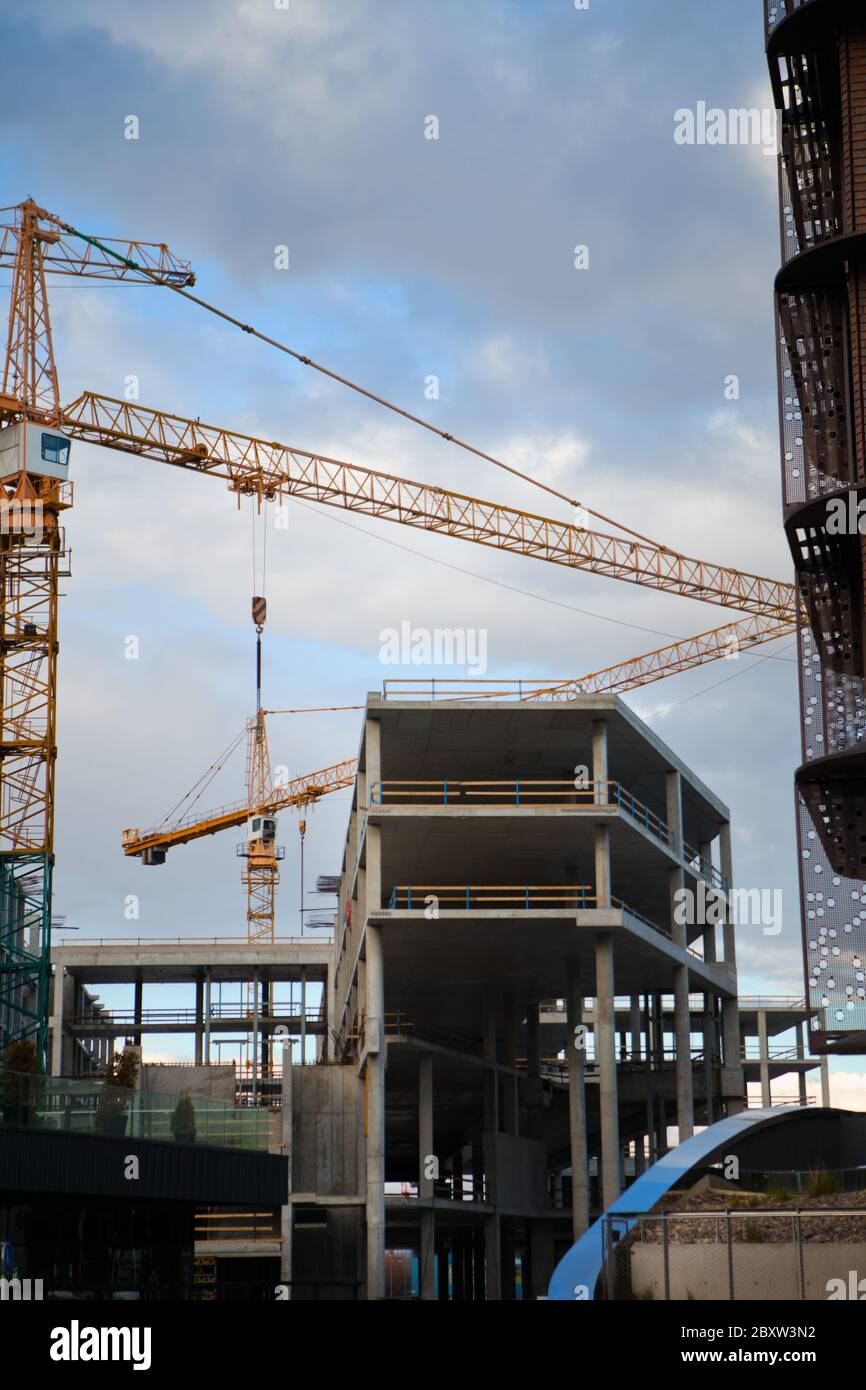 Concrete construction site with two cranes. Blue sky at day time on site. Huge crane rising between two buildings under construction Stock Photo