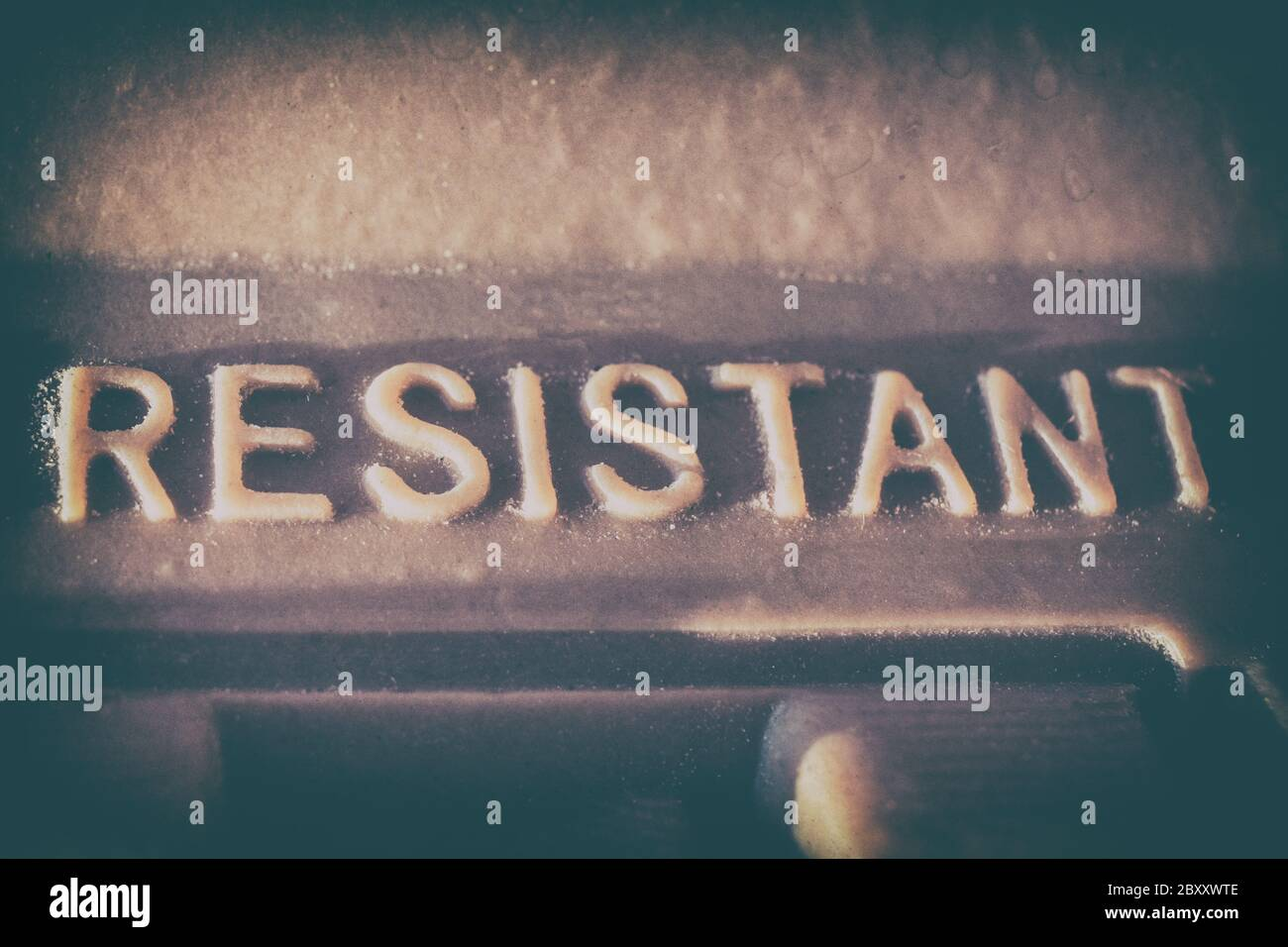 """The word """"RESISTANT"""" written in vintage press stamp Stock Photo"""