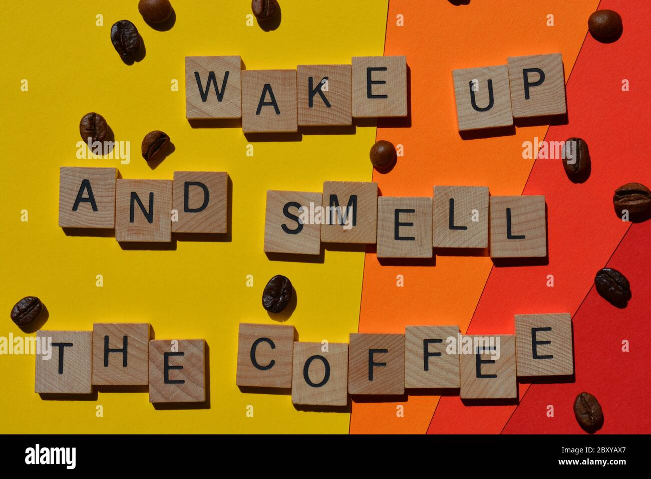 Wake Up And Smell The Coffee, words in 3d wooden alphabet letters with coffee beans isolated on brightly colour background Stock Photo