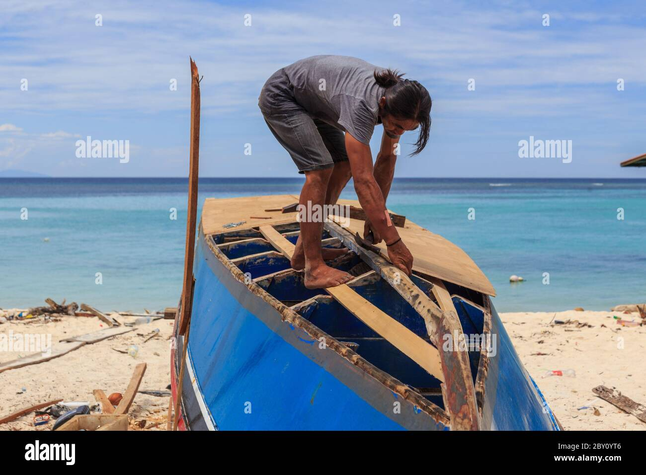 Mantanani Island, Sabah, Malaysia-CIRCA SEPTEMBER, 2017:Unidentified man are hardworking repairing the wooden boat in Mantanani Islan, Kota Belud, Sab Stock Photo