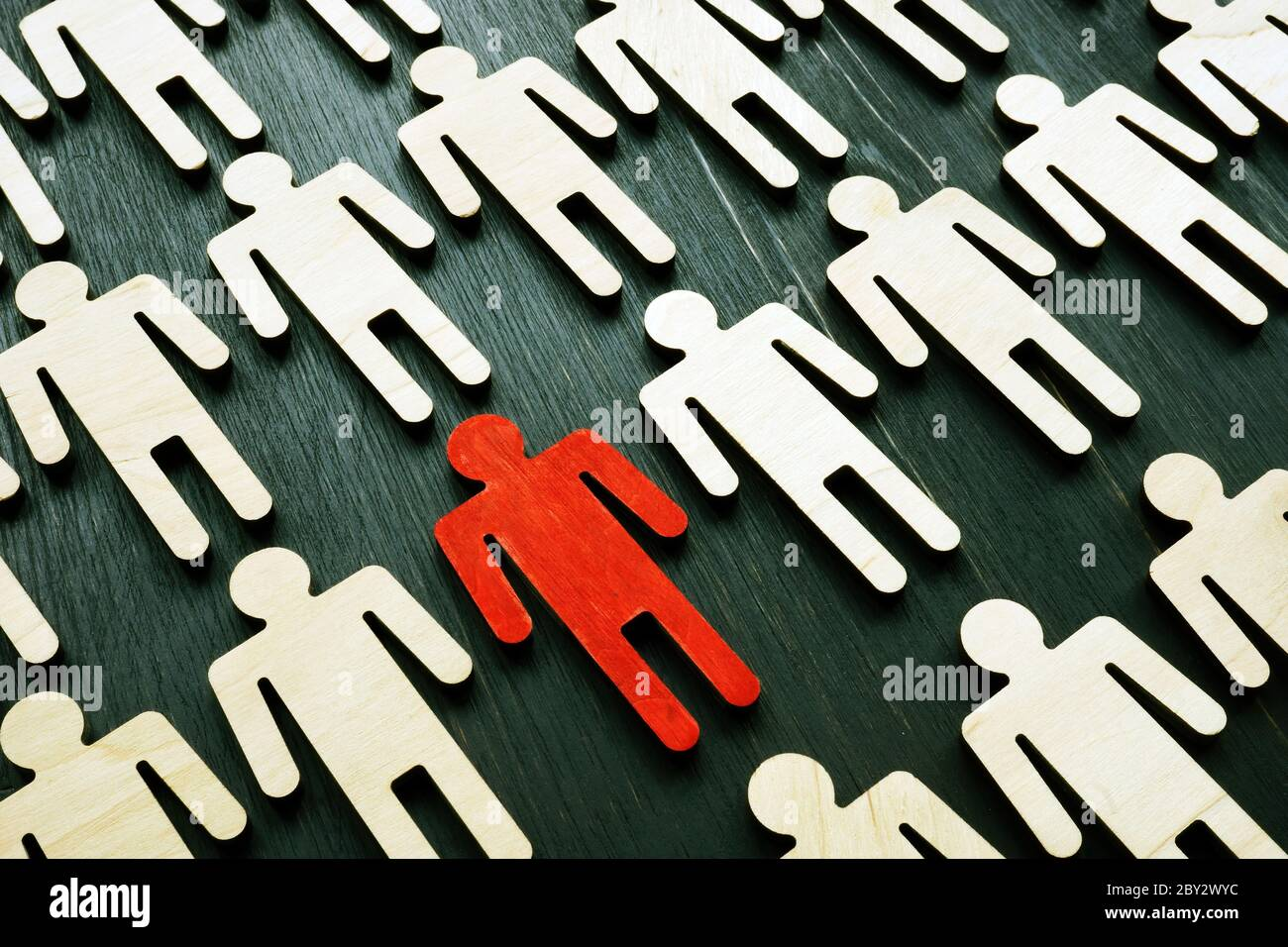 Be unique and different. Crowd from wooden figures and red one. Individuality and independence concept. Think outside the box. Stock Photo