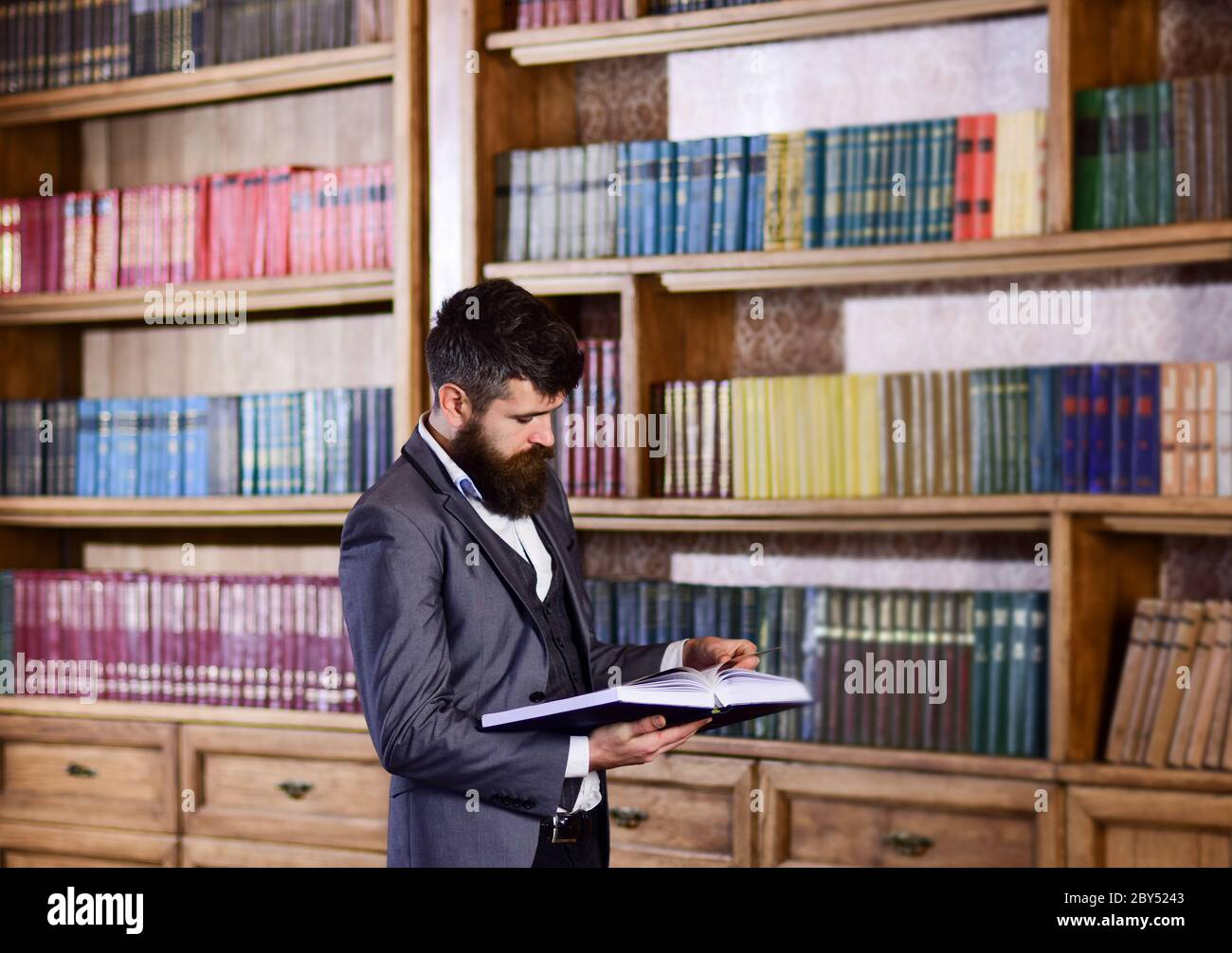 Mature Man With Serious Face Reading Professor Stands In Big Library And Holds Book Bearded Man In Expensive Suit In His Cabinet Study Learn Read Teach Library History Literature Concept Stock Photo