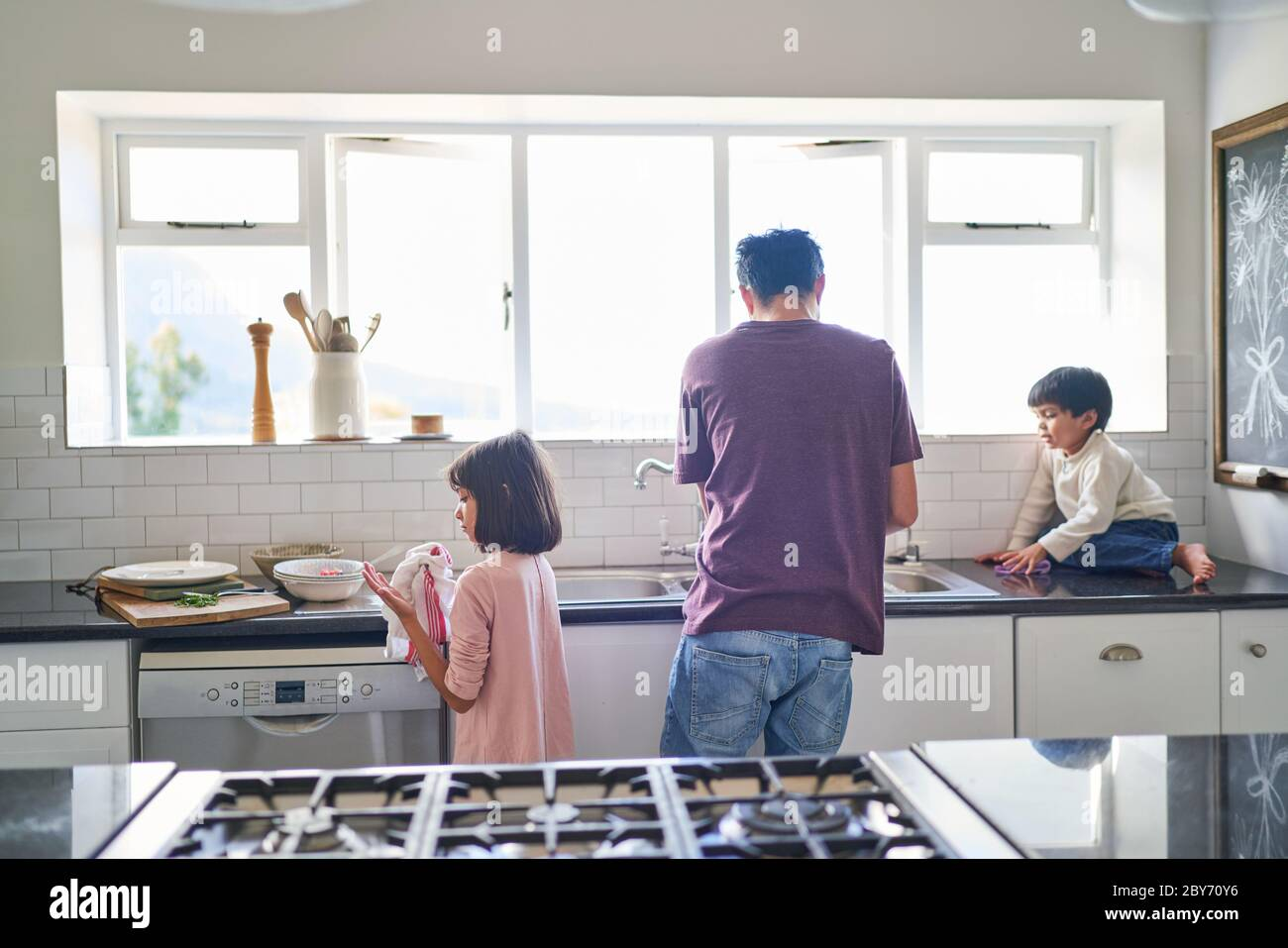 Family doing dishes at kitchen sink Stock Photo