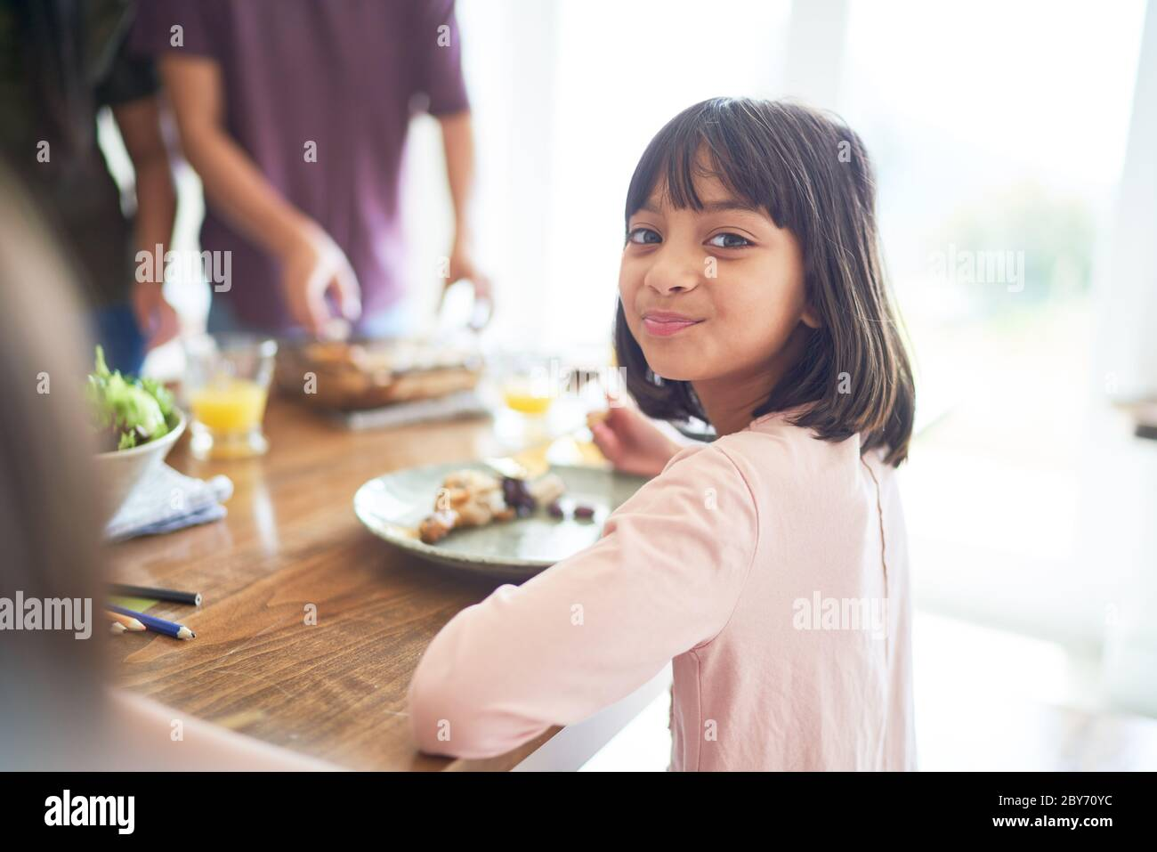 Portrait happy girl eating lunch with family at table Stock Photo