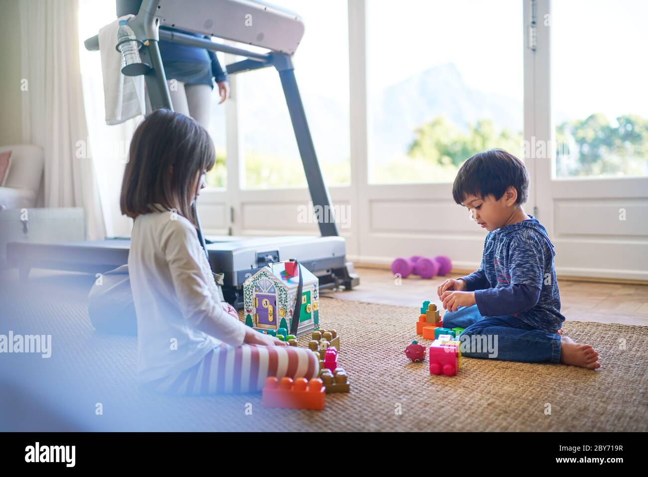 Kids playing with toys on floor by mother on treadmill Stock Photo
