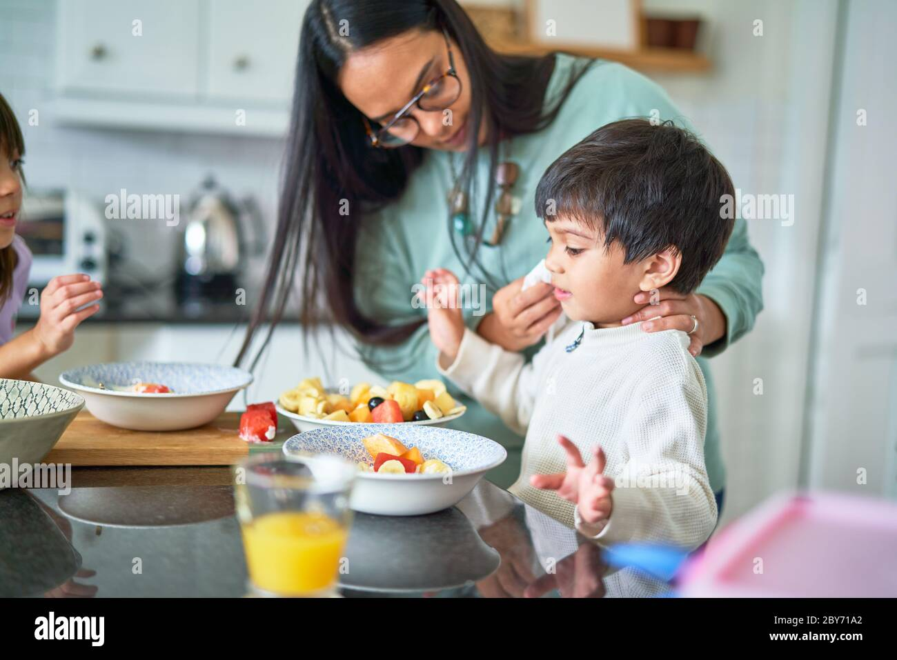 Family eating fruit in kitchen Stock Photo