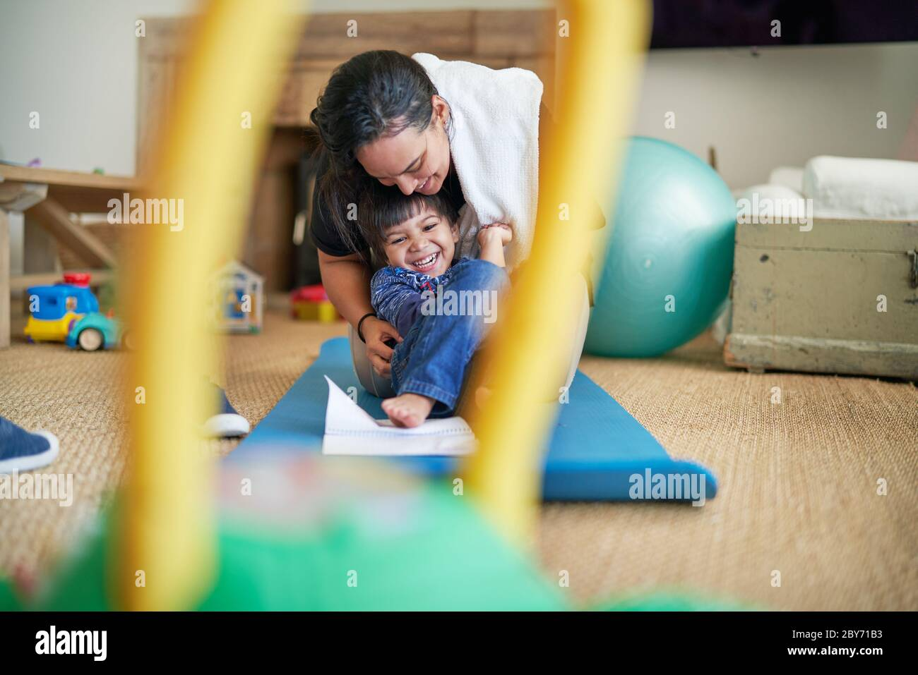 Happy mother and son playing on yoga mat Stock Photo