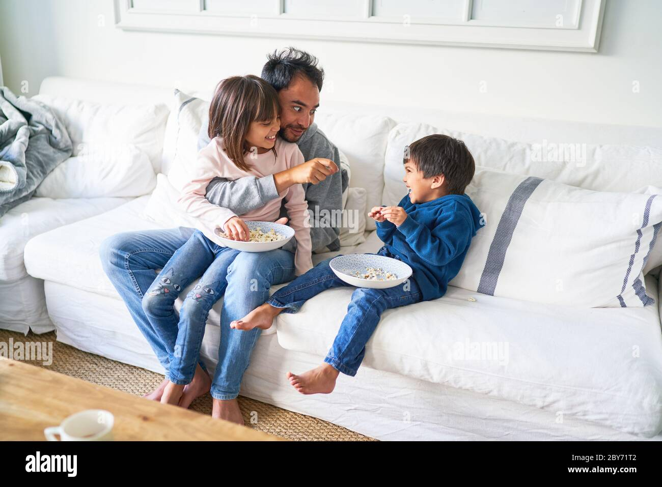 Father and kids eating popcorn on living room sofa Stock Photo