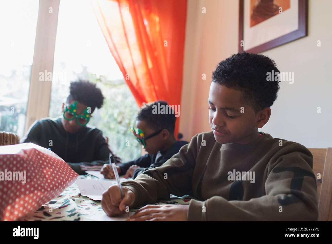 Boy writing Christmas cards at table Stock Photo