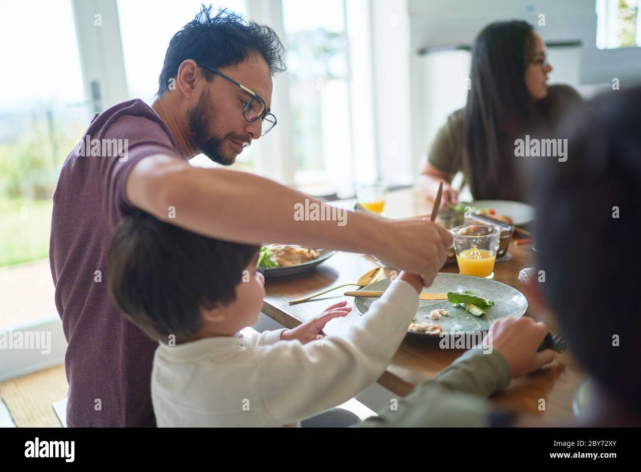Father helping son cut food at dinner table Stock Photo