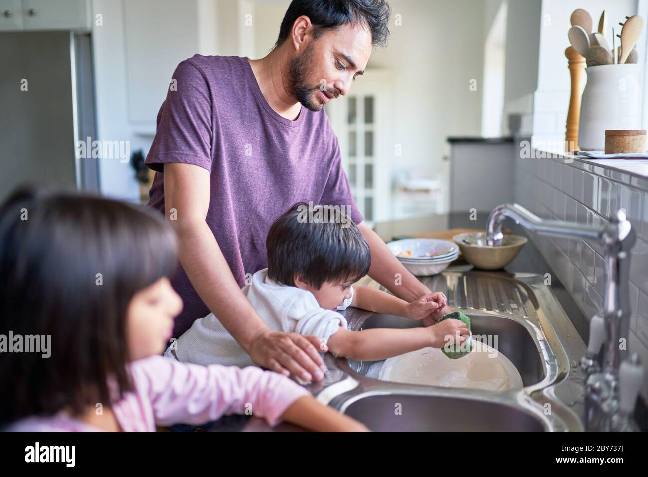 Father and kids doing dishes at kitchen sink Stock Photo