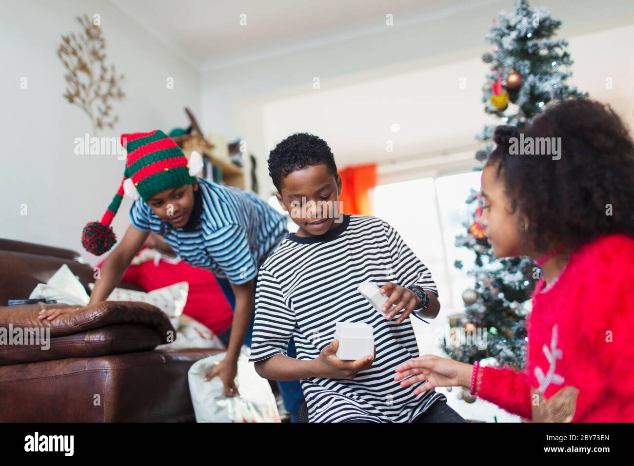 Family opening Christmas gift in living room Stock Photo