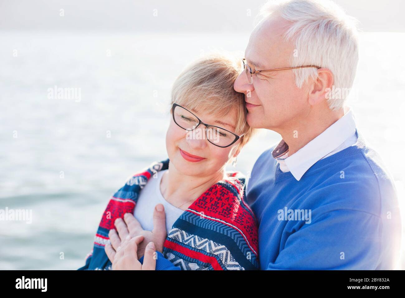 Senior couple is enjoying retirement and life at sea beach outdoor. Happy man and woman are hugging, embracing Stock Photo