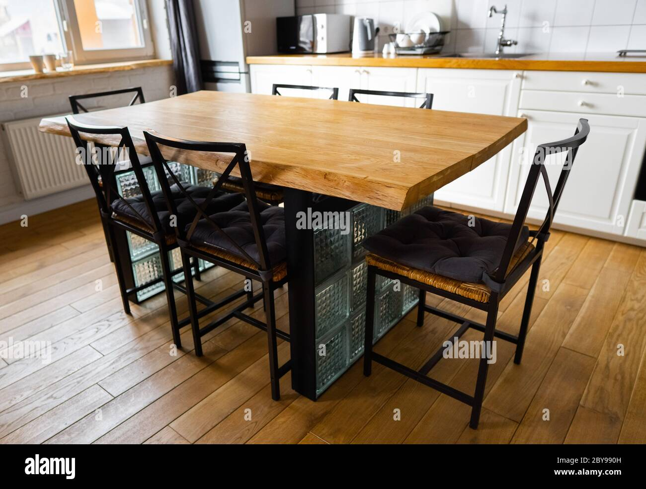 A Big Wooden Dining Table With Glass Blocks And Metal Wicker Chairs And Pillows In Modern Scandinavian An Eat In Kitchen Against Bright White Stock Photo Alamy