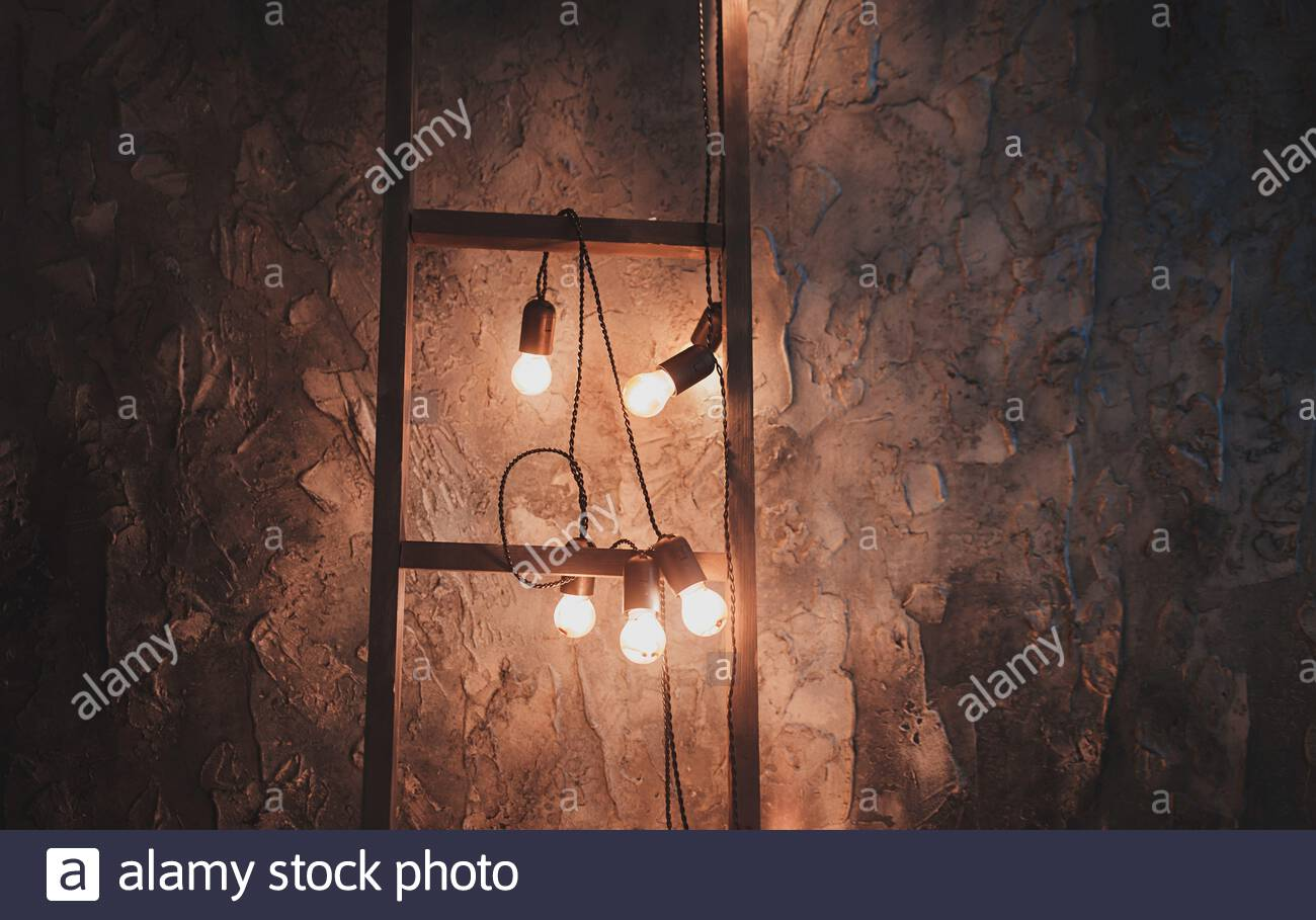 Many Bright Light Bulbs Hang On A Ladder In The Loft Interior Stock Photo Alamy
